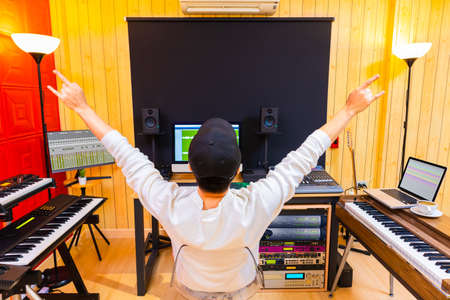 back of asian male music producer showing rock hand gesture while enjoy listening his song in home recording studio