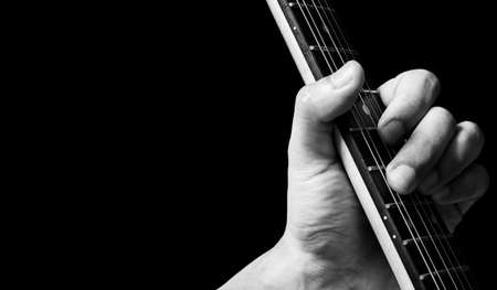 close up male musician left hand playing chord on electric guitar neck. music background
