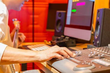 male musician recording electric guitar track on computer, focus on hand. music production concept Stock fotó
