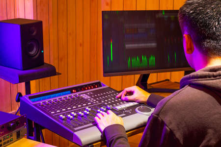 back of asian professional sound engineer mixing audio signal on control surface mixing console in broadcasting, recording studio