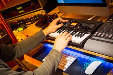male professional music producer hands arranging a hit song on keyboard and computer in home studio. music production concept