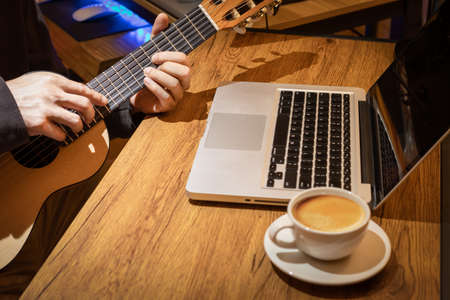 music vlogger streaming a live video while playing acoustic guitar and having a good time with coffee
