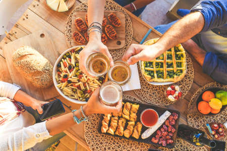 Toast with friends, dinner on the terrace in joy, aperitif at the end of summer with beer and pretzels, joy and parties. Hands that hold various glasses. Togetherness, celebration, carefree concept. Standard-Bild