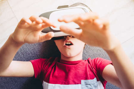 Young man having fun with virtual reality goggles technology lying on sofa at home. Astonished boy gesticulates wearing vr headset. Tech, modern lifestyle and joyful youth concept. Focus on teen mouth