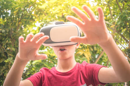 Young man having fun with virtual reality goggles technology outdoor in the park. Astonished boy gesticulates wearing vr headset. Tech, modern lifestyle and joyful youth concept. Focus on teen mouth.
