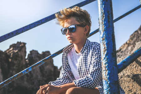 Serious trendy boy sitting on a staircase looking at the horizon waiting friends. Portrait of a thoughtful young male relaxing outdoor. Pensive teen casual clothed enjoying summer holiday alone.