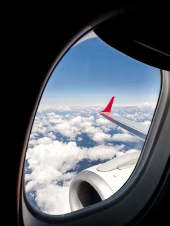 View outside the porthole of a wing of a modern airplane flying over the clouds with blue sky. View from the aircraft window during a tourist flight. Travel, tourism, transport and freedom concept.
