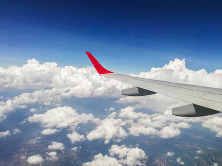 White wing of a modern airplane flying over the clouds with blue sky in background. Panorama view from the aircraft window during a tourist flight. Travel, tourism, transport and freedom concept. Stock fotó