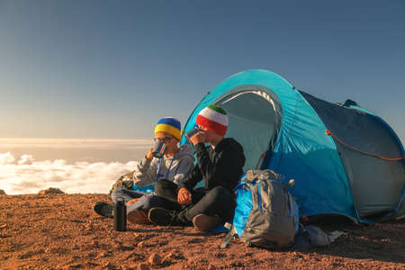 Two boys toast drinking cups of tea sitting in a camping tent. A couple of young tourists enjoying high mountain with blue sky and clouds in background. Adventure trip togetherness and open air concept