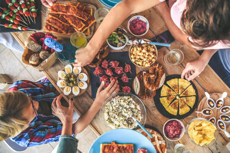 Evening with friend dinner on the terrace enjoying together. Summer aperitif with group of friends Joy and festivities in family View from the top of a table with many foods Happy hands taking viands 免版税图像
