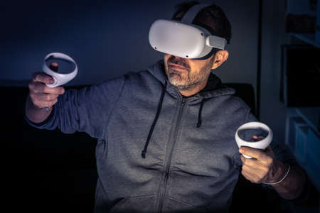 Man playing with virtual reality device. Cyberpunk futuristic mood, immersive experience with video game and VR 3D viewer technology. People using next-generation electronic devices. Tech concept Фото со стока