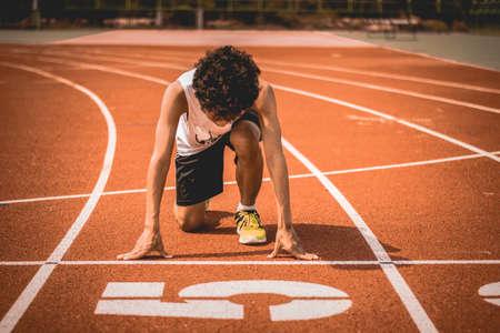 Sport man running on a racetrack