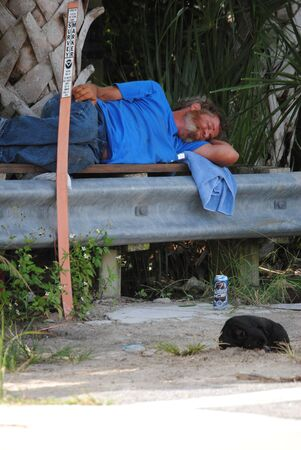 passed out: homeless man sleeping on a bridge Editorial