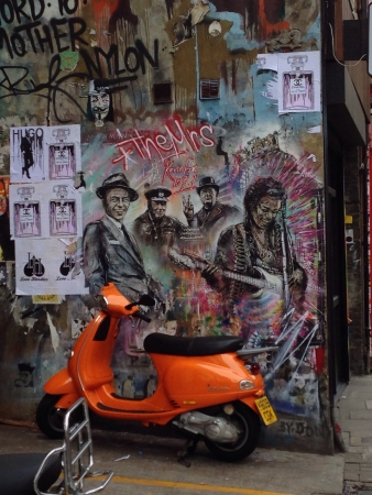A Wall of Graffiti Art and Flyers with an Orange Scooter at Brick Lane London