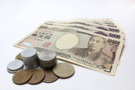 Piles of Japanese currency Yen coins and banknotes on white background