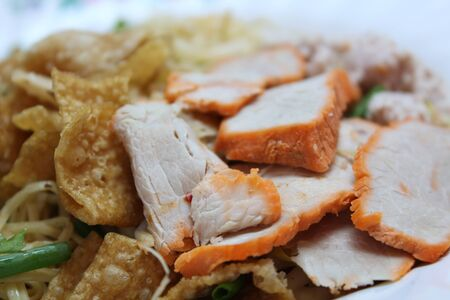 Close-up view of dried egg noodles in a bowl mix topping with red pork, minced pork, onion and fried wonton sheet, Chinese cuisine