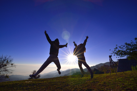 jag: A happy jumping couple in the sunshine morning in silhouete style Stock Photo