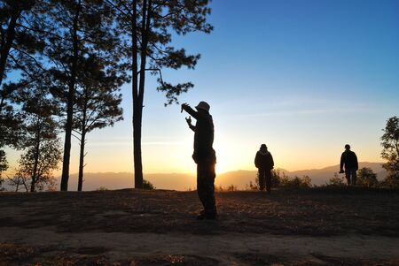Travellers standing in the sunrise morning with silhouete landscape style Stock Photo