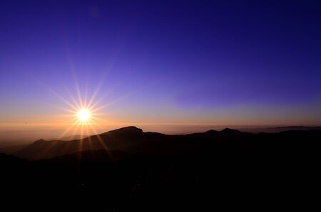 A sunrise above a mountain peak looks very warm in a calm down morning 版權商用圖片