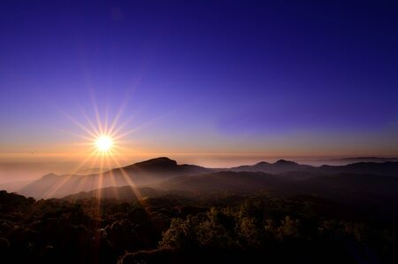 A power of sunrise above a mountain peak looks warm in a calm morning
