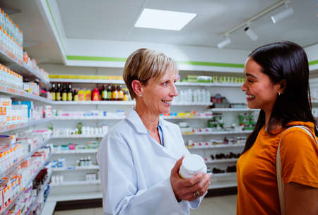 Caucasian senior pharmacist assisting mixed race patient giving advice on dosage intake while standing in pharmacy