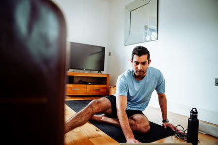 Mixed race male working out from home sitting on lounge floor following program on laptop Stock Photo