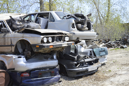 Scrap Cars piled on op of each other in a junk yard