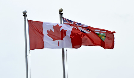 A Canadian Flag (National Flag of Canada) and Ontario flag (provincial flag) fly next to each other in Kingston, Ontario. Isolated on white cloudless background.