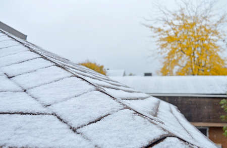 Snow freshly falling on the top of roofs and homes in late autumn. 스톡 콘텐츠