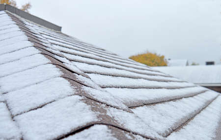Freshly fallen snow on a roof top with additional homes in the background, intentionally blurred
