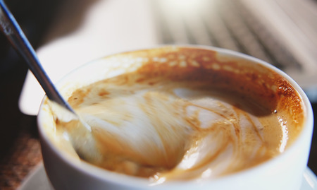 Mixing organic sugars into a cup of latte coffee, slow motion.