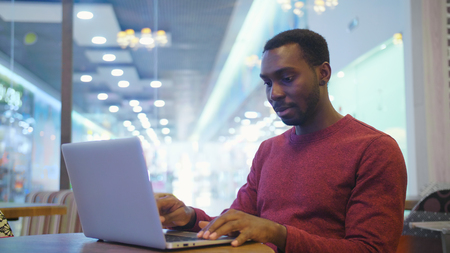 Portrait of happy african businessman sitting in a cafe and working on laptop
