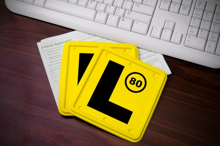 l plate: Two L plates and Licence Application laying on the computer desk next to the white keyboard.