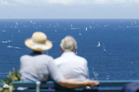 yacht race: Una pareja de ancianos sentados en el banquillo y ver una carrera de yates