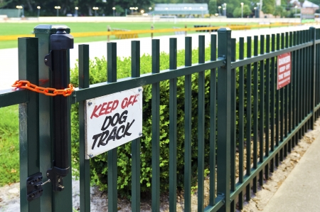 Keep off dog track sign on the green fence. photo