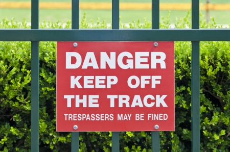 trespasser: Red keep off sign on the fence