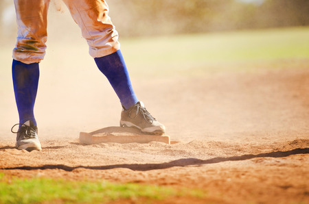 Baseball player wearing blue socks standing on a baseball base. 스톡 콘텐츠