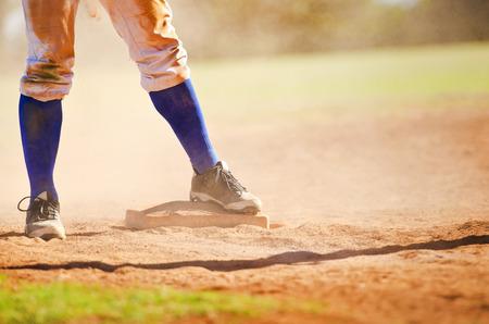Baseball player wearing blue socks standing on a baseball base. Foto de archivo