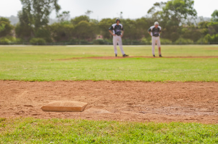 Image of a third base with two baseball players in the background