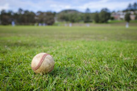 Wide angle shot of used baseball laying on fresh green grass with baseball players in the background