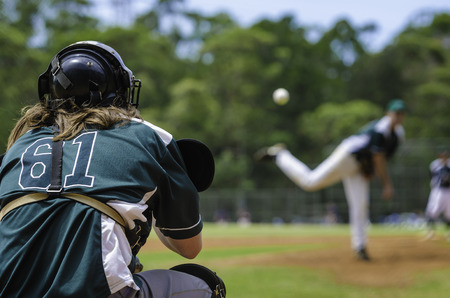 A baseball catcher looks at a flying ball during a game.