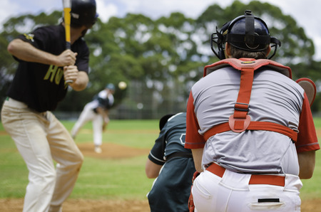 Baseball pitcher throwing ball to batter watched by Umpire and Catcher.