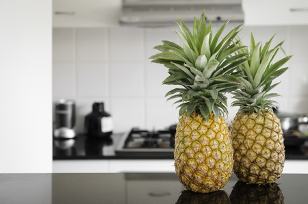 kitchen bench: A two whole pineapples sitting on a kitchen bench