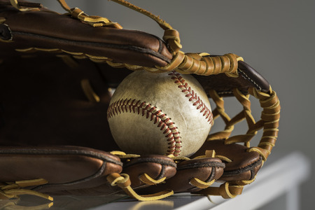 guante de beisbol: Close-up of a used baseball ball inside brown, leather baseball glove on plain, grey background.