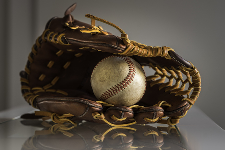 Close-up of a used baseball ball inside brown, leather baseball glove on plain, grey background.