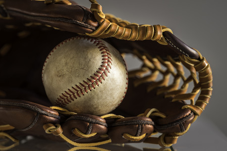 baseball glove: Close-up of a used baseball ball inside brown, leather baseball glove on plain, grey background.