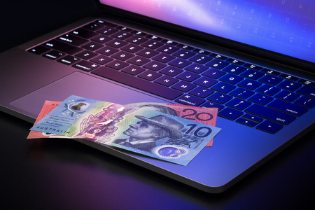 Australian dollar banknotes on laptop