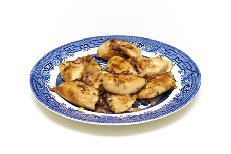 Varenyky, vareniki, pierogi, pyrohy or dumplings, filled with cheese and potatoes, served with onion and bacon on a blue plate Stock Photo