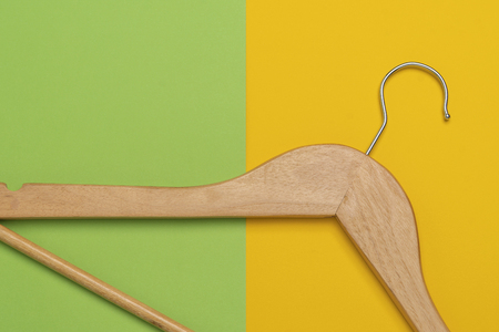 Closeup of a wooden clothes hanger isolated on a green and yellow background Foto de archivo