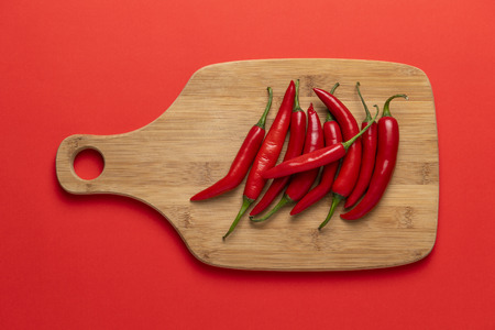 Group of red narrow long spicy chili peppers on the wooden chopping board on red background